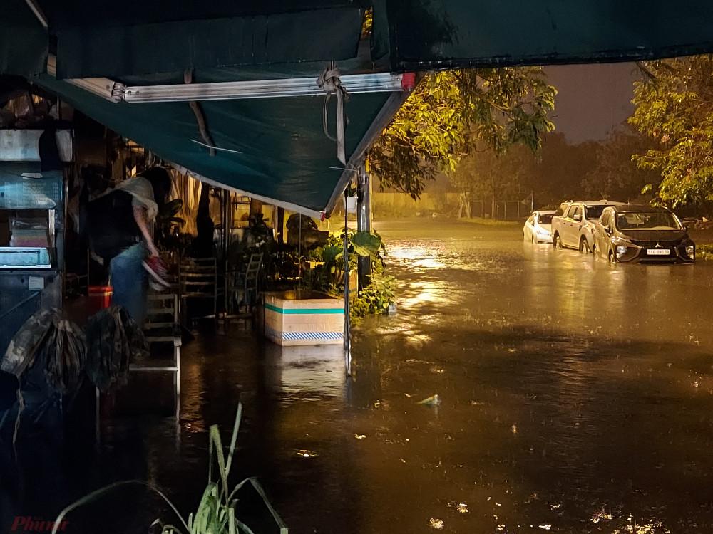 Đường vào Khu tái định cư Phú Định cũng bị nước ngập nhấn chìm. Một phụ nữ đi làm về muộn không dám lội nước ngập vào nhà phải đứng chôn chân trên chiếc ghế của quán cà phê đã đóng cửa