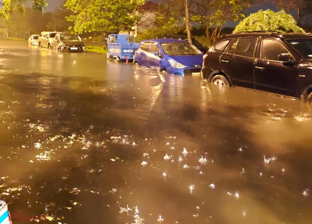 Nước ngập lênh láng trên đường khiến xe ô tô gửi ngoài trời của chung cư Ehome 3 bị nước ngập nhấn chìm. Người dân lo lắng nếu mưa kéo dài hết đêm nay nước ngập sẽ làm nhiều phương tiện bị hư hỏng.