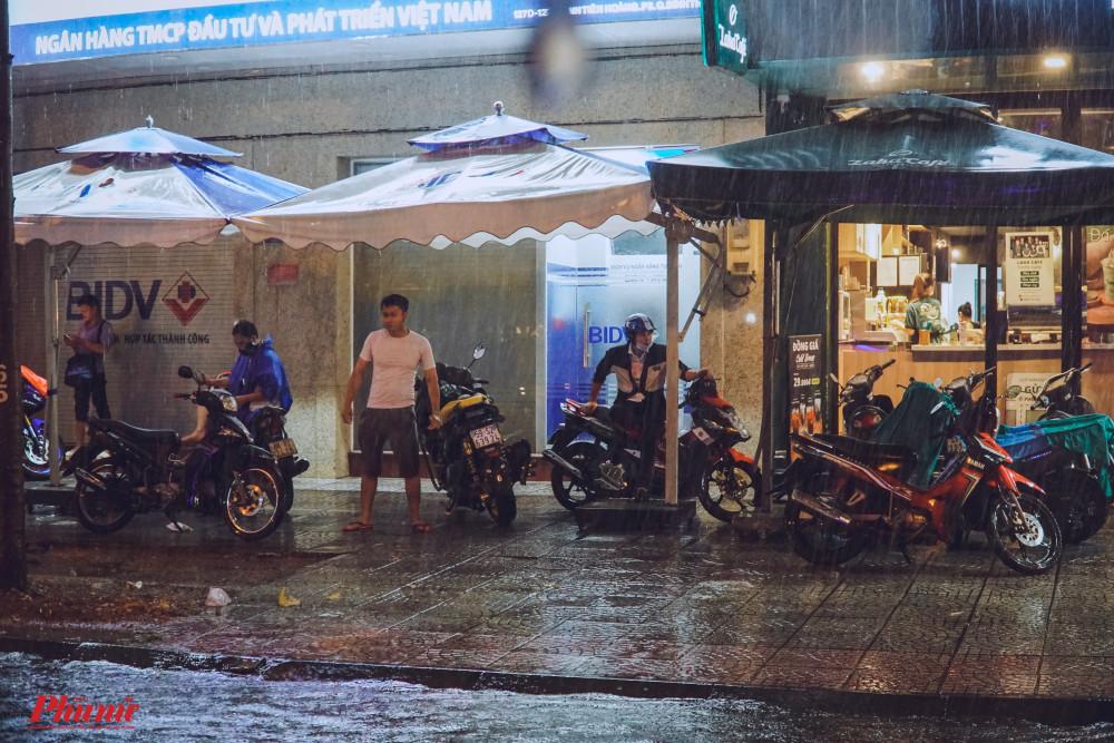 Mái hiên các nhà ven đường thành nơi trú mưa cho nhiều người