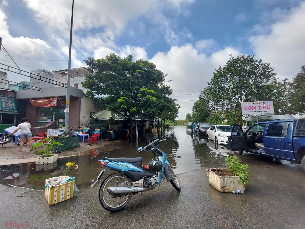 Người dân dùng thùng xốp, chậu cây, xe máy để cảnh báo cho người dân ở xa hạn chế lưu thông vào cung đường đang bị ngập sâu.