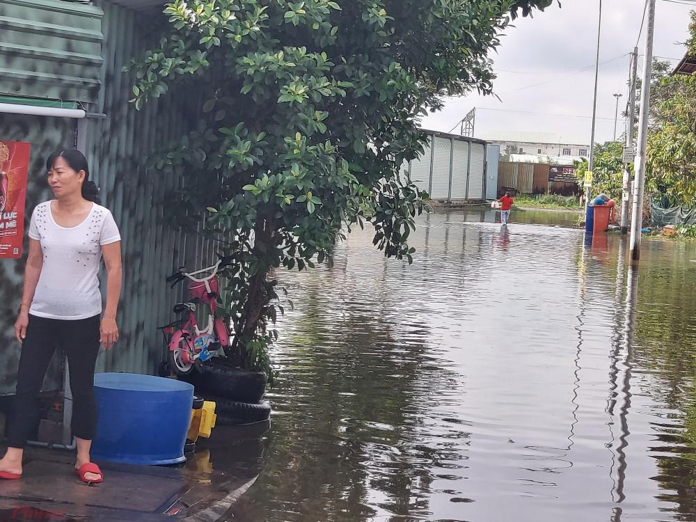 Con đường chính dẫn vào khu dân cư bị nước ngập khoảng nửa mét gây ảnh hưởng đến việc di chuyển của người dân.
