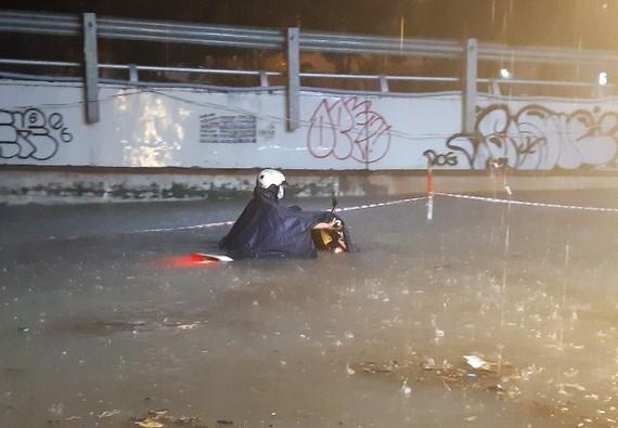 Đường Nguyễn Hữu Cảnh đã ngập quá yên xe của người tham gia giao thông trong trận mưa tối quá