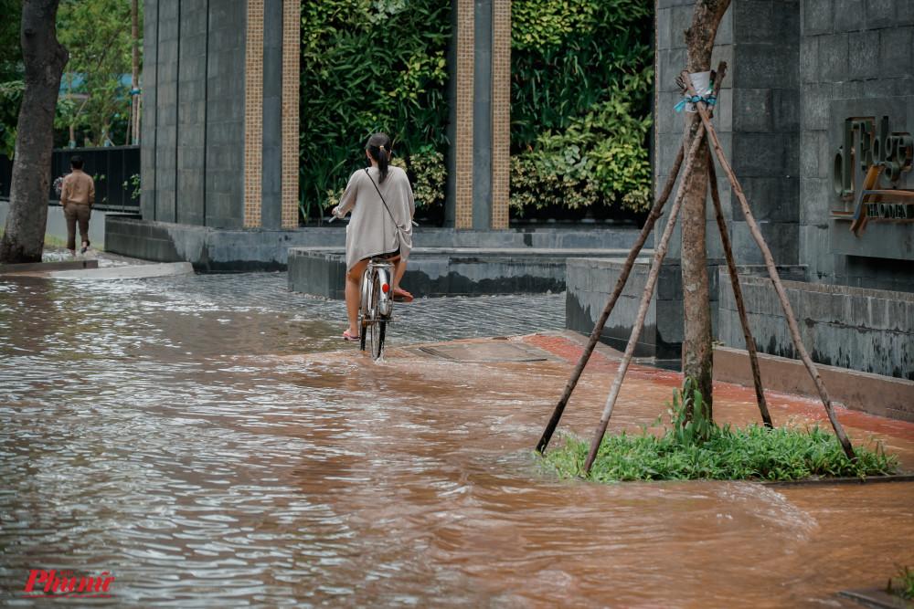 12 giờ trưa ngày 7/8 mực nước ngập tại đường Quốc Hương vẫn hơn bánh xe, người dân phải di chuyển trên vỉa hè