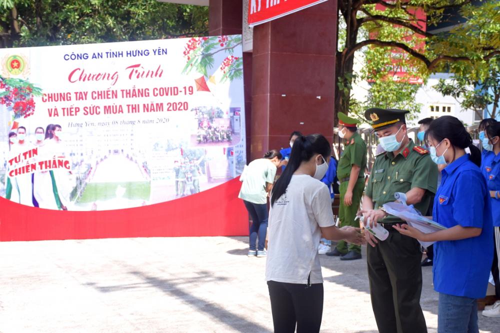 Các chiến sĩ công an tỉnh Hưng Yên cùng lực lượng tình nguyện đo thân nhiệt, sát khuẩn cho thí sinh - Ảnh: Văn Hải
