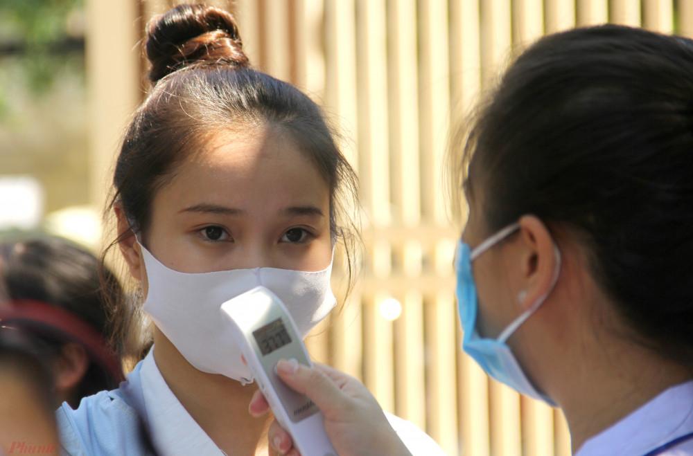 Các thí sinh được sát khuẩn, đo thân nhiệt trước khi vào thi