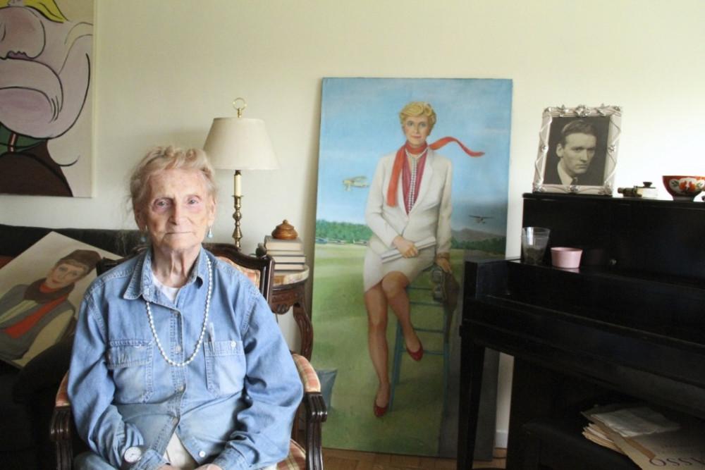 Cụ bà Robina Asti bên cạnh bức chân dung thuở thiếu thời sau khi đã chuyển giới từ một chàng trai thành một thiếu nữ. Ảnh: mezipatra