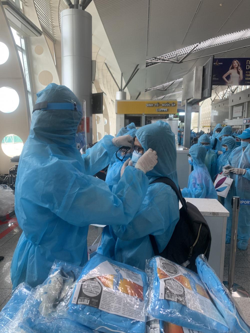 Hành khách được mặc đồ bảo hộ kín mít để tránh lây nhiễm virus SARS-CoV-2 nếu có.
