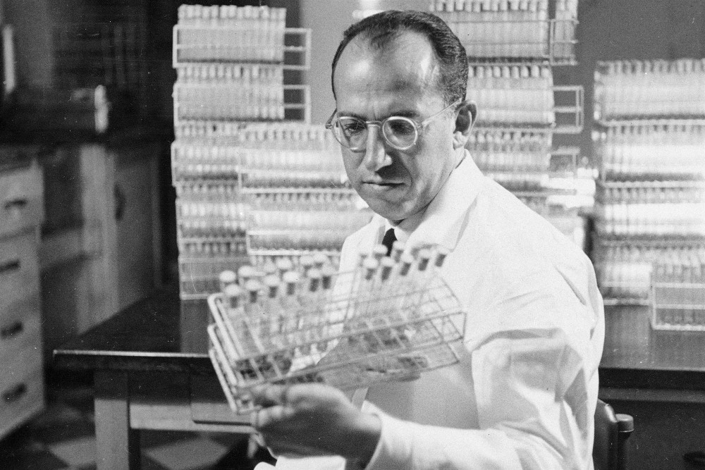 Tiến sĩ Jonas Salk, cha đẻ của vắc-xin phòng virus bại liệtliệt, đang cầm trên tay mẻ vắc-xin thử nghiệm được bào chế tại phòng lab ở Đại học Pittsburgh năm 1954. Ảnh: AP