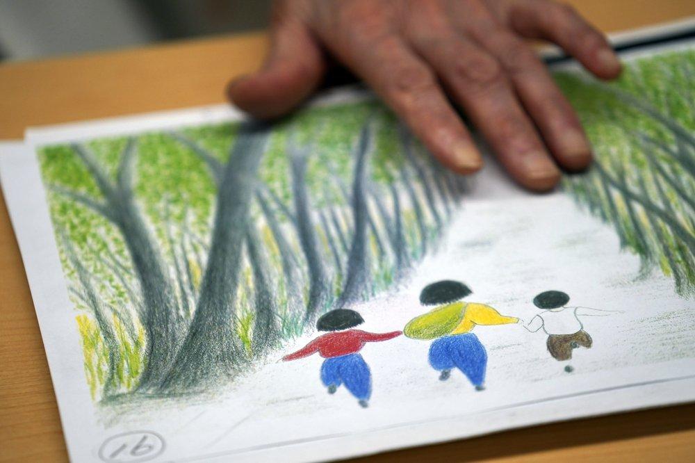 Một bức tranh vẽ của bà Mitsuyo Hoshino thể hiện cảnh những đứa trẻ mồ côi dắt tay nhau chạy trốn.