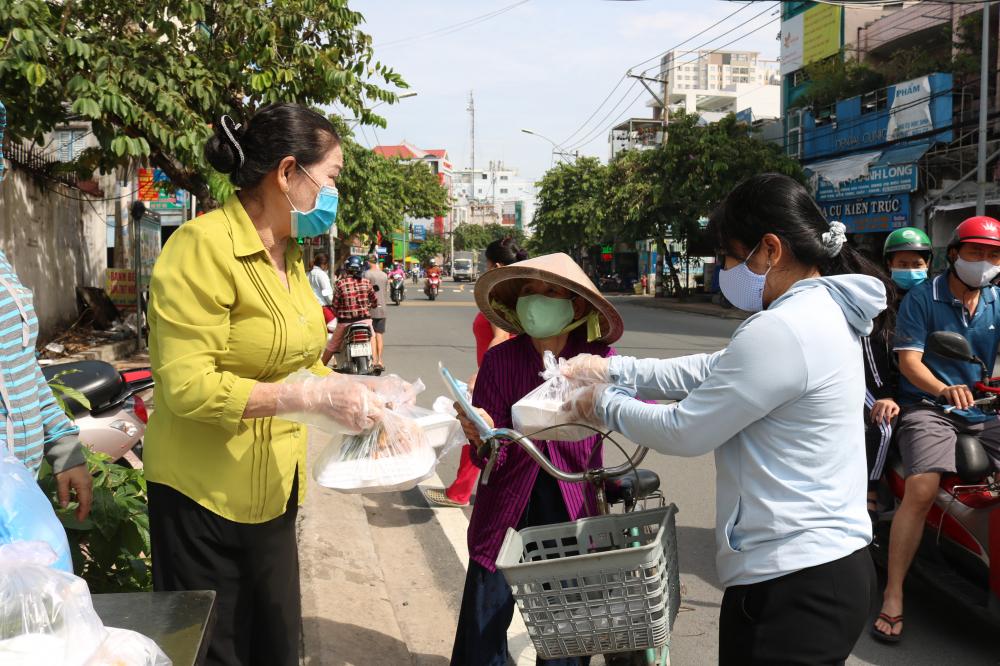 Cơm canh nóng sốt đến tay bà con có hoàn cảnh khó khăn, khách vãng lai đi ngang đoạn đường Đặng Văn Bi vào sáng 15/8.