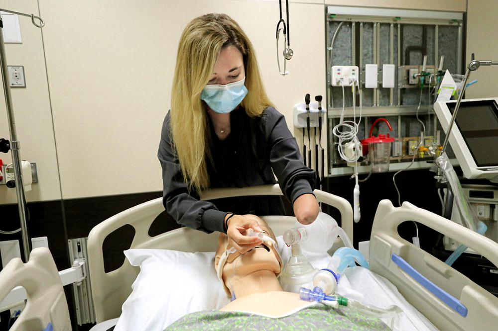 """""""Cô Tấm"""" một tay Savannah Stuard thực hiện các kỹ thuật điều trị bệnh nhân COVID-19 trên hình nộm tại Trung tâm Y tế Ochsner (New Orleans) - Ảnh: AP"""