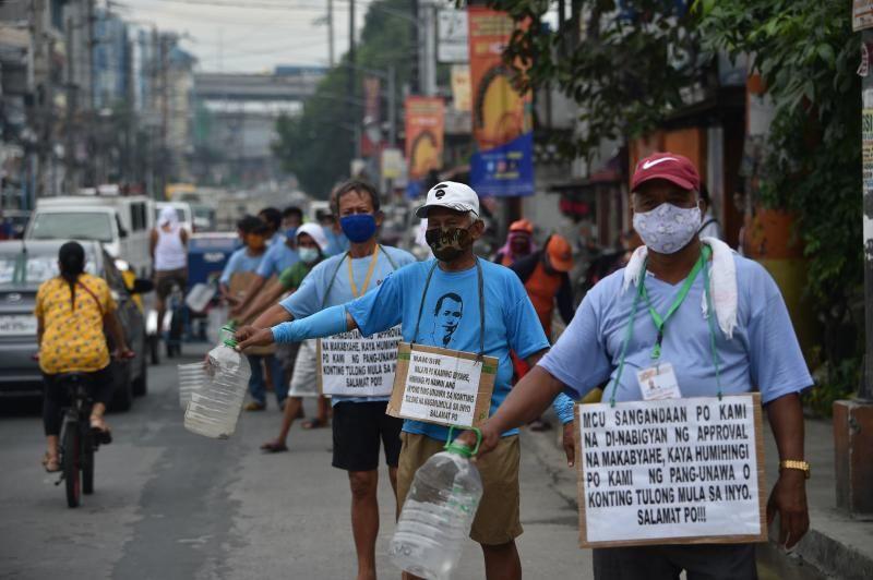 Một nhóm các tài xế lái xe jeepney trên đường phố thủ đô Manila, đeo trên người tấm bảng với dòng chữ Làm ơn. Chúng tôi đói - Ảnh: AFP