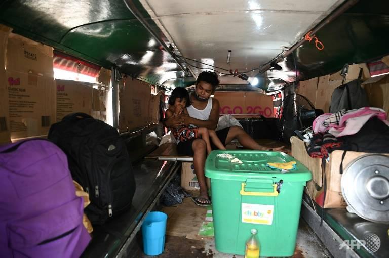 Anh Flores cùng đứa con gái nhỏ của mình bên trong căn phòng tạm bợ được cải tạo từ chiếc xe jeepney của mình - Ảnh: AFP
