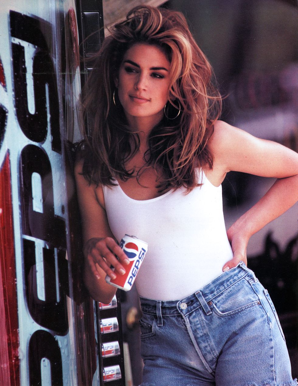 Năm 1992, Cindy Crawford, 1992 Siêu mẫu tạo dáng trong trang phục denim lưng cao ôm sát hông bên ngoài bộ bodysuit trắng trong quảng cáo Pepsi Super Bowl mang tính biểu tượng này.