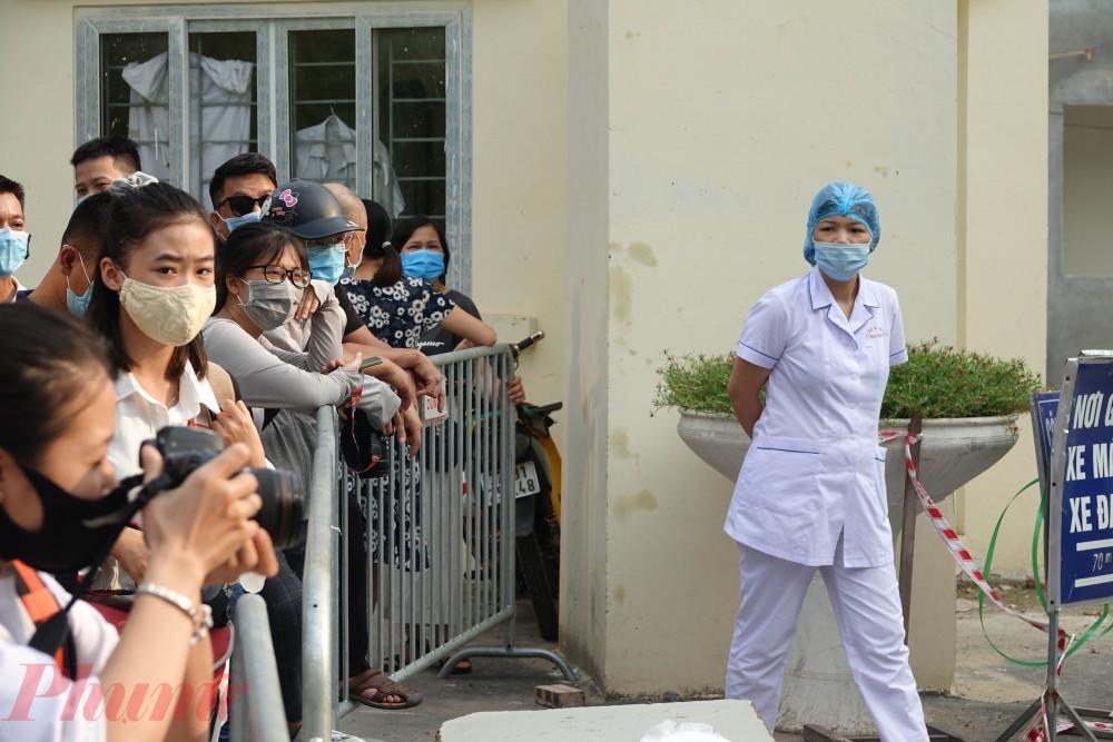 Người thân của các bệnh nhân cũng chờ đợi ở phía bên kia hàng rào, chờ vào thăm, chăm sóc người thân.