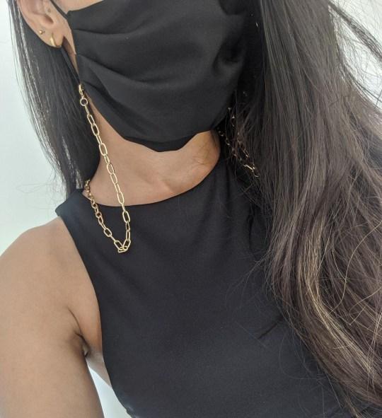 Dây chuyền vàng kết hợp với khẩu trang đen đi cùng với bộ trang phục trông rất thời trang