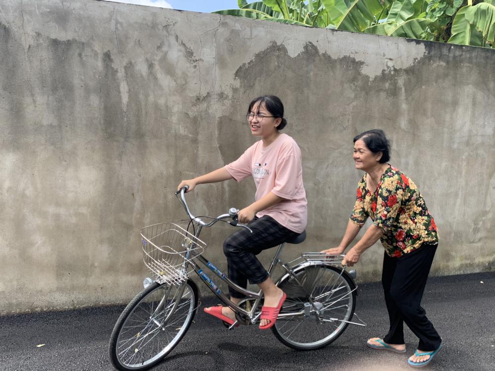 Tường Vy được bà nội hướng dẫn tập chạy xe đạp.