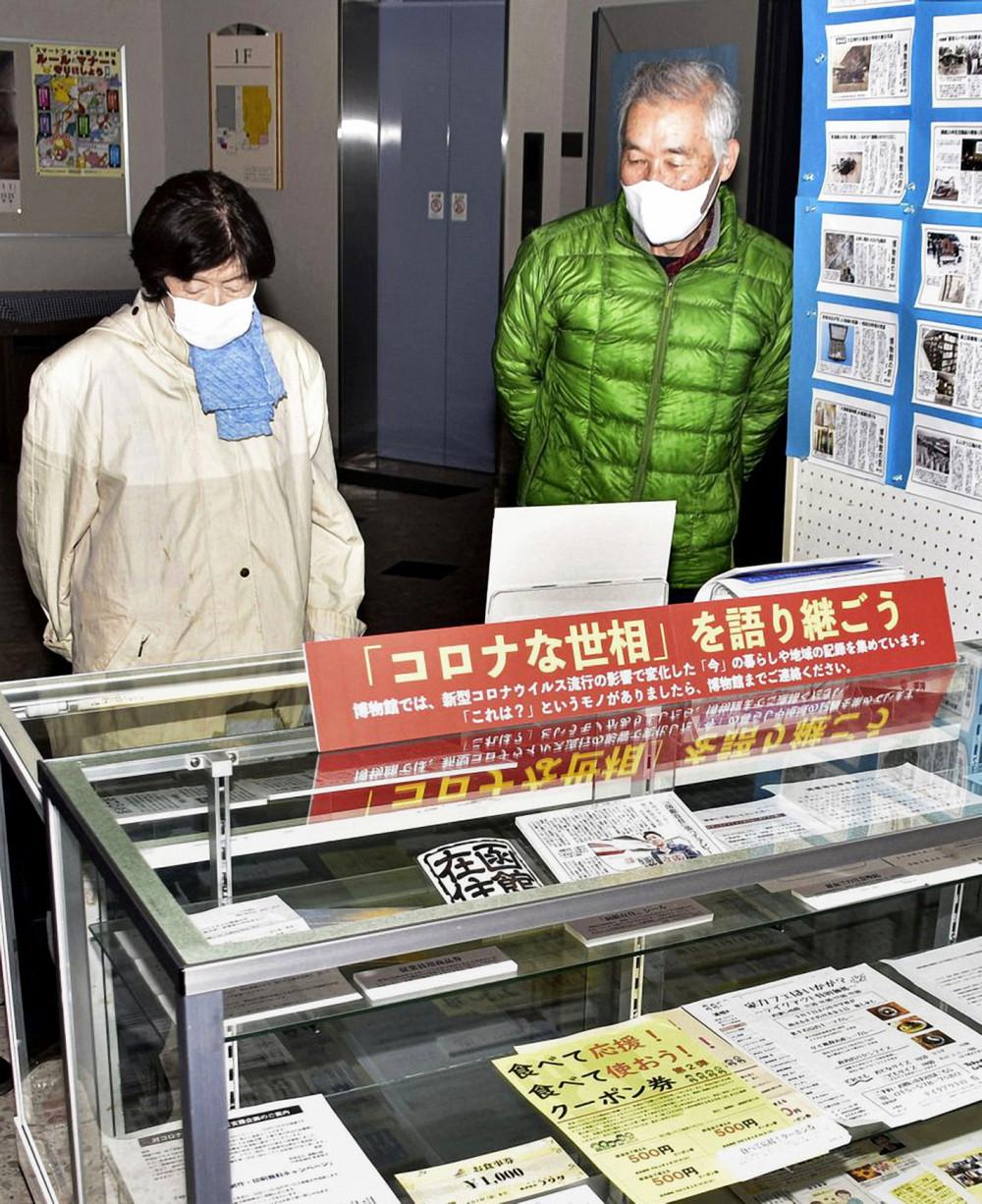 Khách tham quan xem trưng bày liên quan đến COVID-19 tại Bảo tàng Lịch sử Urahoro, Hokkaido - Ảnh: Kyodo News