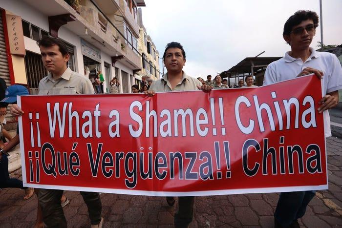 Người dân Ecuador biểu tình phản đối Trung Quốc sau khi hải quân nước này bắt được một tàu gắn cờ Trung Quốc chở theo 300 tấn cá đánh bắt trái phép ngày 14/8/2017 - Ảnh: AP/Getty Images