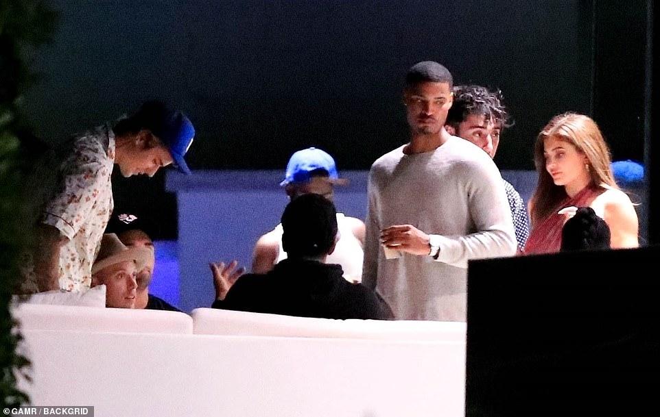Hình ảnh Justin Bieber bên cạnh một nhóm khách tại bữa tiệc.