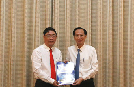 Ông Đinh Minh Hiệp (bìa trái) nhận quyết định điều động và bổ nhiệm từ UBND TP
