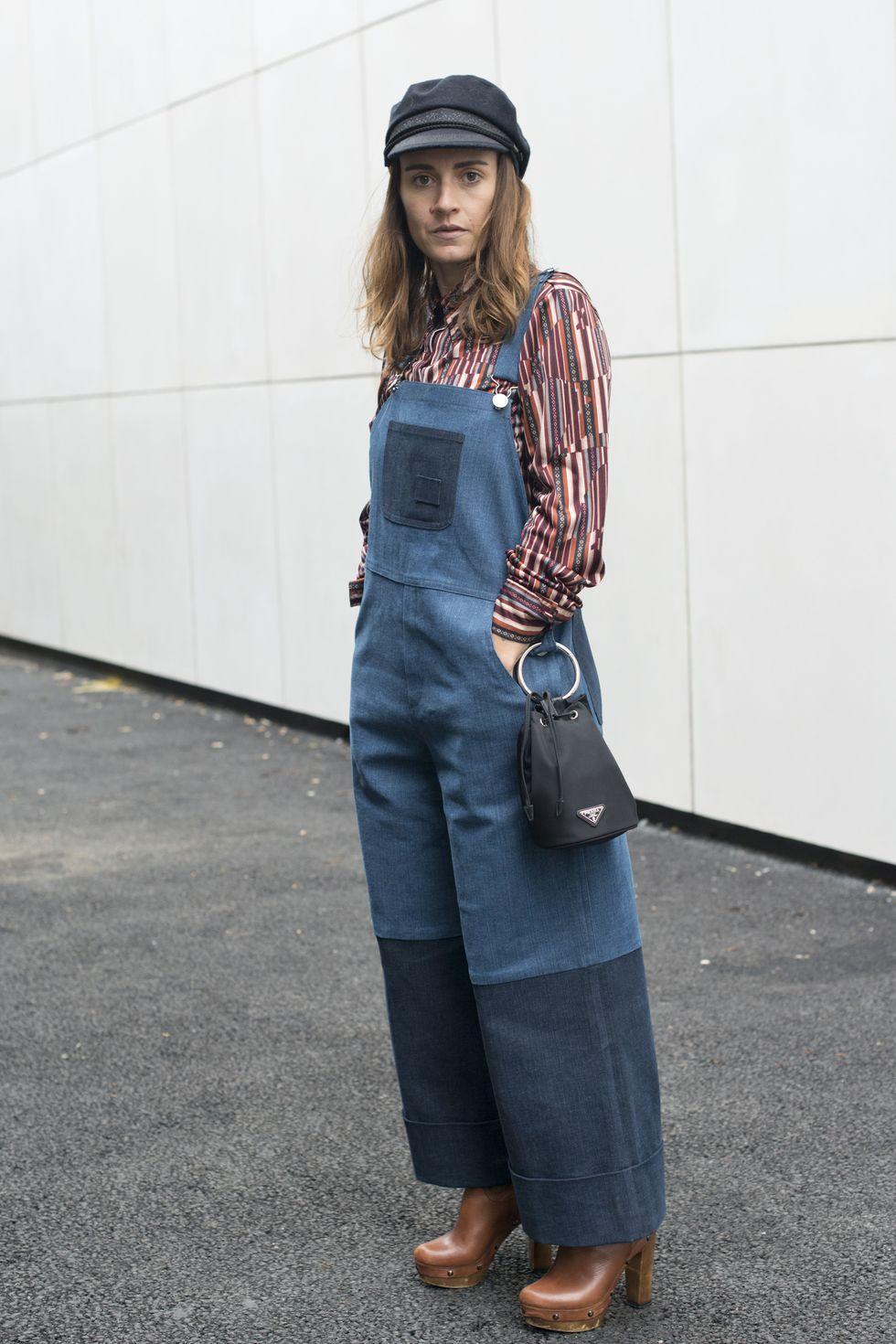 Ngôi sao phong cách đường phố Sara Reverberi đã mang đến cảm giác châu Âu đầy nghệ thuật trong chiếc quần yếm denim của cô. Cô ấy tạo kiểu cho chiếc áo một mảnh với chiếc mũ lưỡi trai, phần trên in hình trừu tượng và đôi giày lấy cảm hứng từ guốc. Cô gắn chiếc túi Prada của mình vào một chiếc vòng trên chiếc quần yếm hai dây.