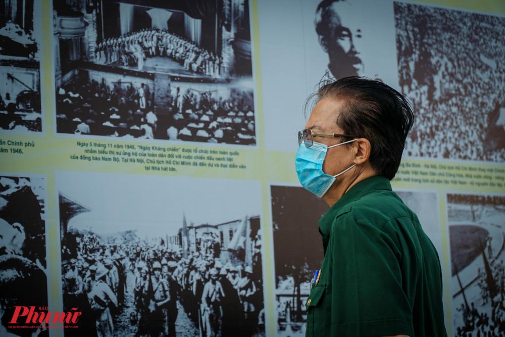 Một cựu chiến binh trầm tư bên những tấm ảnh tại buổi triển lãm.