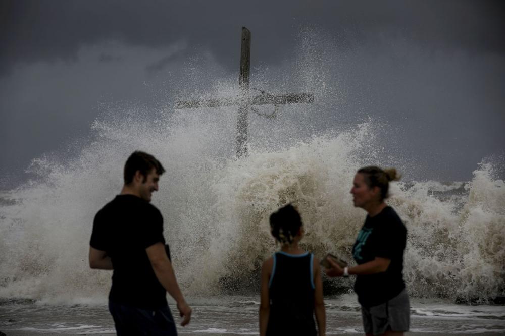 Người dân bàn tán khi sóng xô vào bờ và các dải hội tụ của bão Laura mang theo mưa gió đến ở Đảo High, bang Texas.