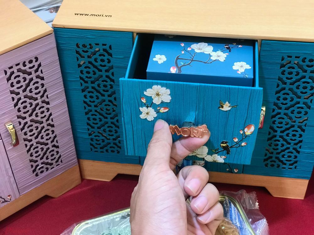 Một hộp bánh bằng gỗ có hai màu xanh, hồng khá sang trọng.