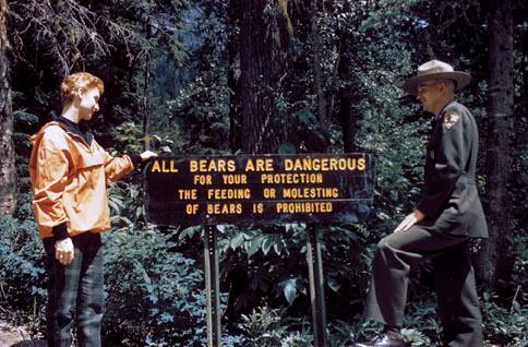 Một du khách (áo cam) đang cùng nhân viên kiểm lâm đọc bảng cảnh báo gấu khi tham quan công viên quốc gia Glacier, Montana. Nơi đây là một trong những địa điểm tập trung nhiều gấu ở Mỹ.