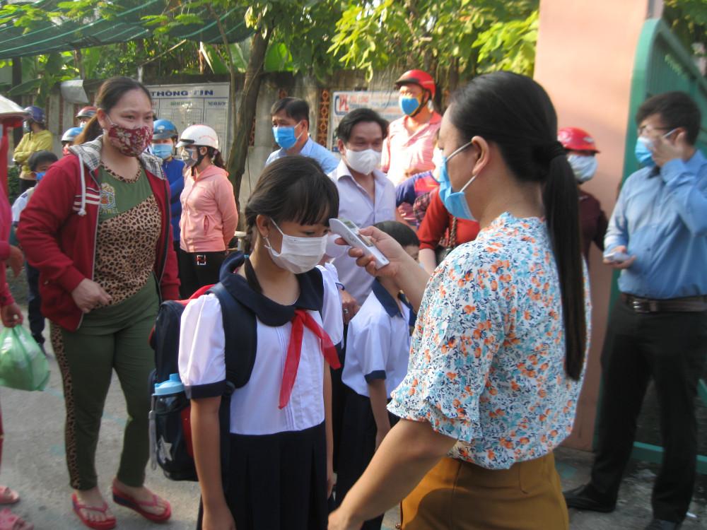 Học sinh được đo nhiệt độ, sát khuẩn tay trước khi bước vào cổng trường