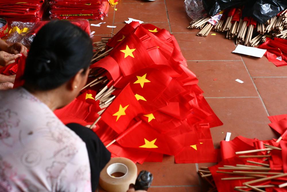 Mẹ anh Phục đang dập ghim cho những lá cờ
