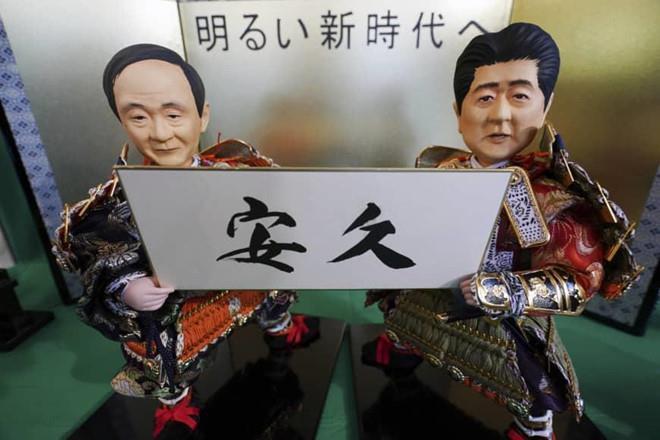 Búp bê truyền thống Nhật theo hình của Chánh văn phòng Nội các Nhật Bản Yoshihide Suga (trái) và Thủ tướng Shinzo Abe đang cầm một cái tên được đồn đoán của triều đại Nhật hoàng Naruhito sắp lên ngôi. Ảnh: AP.