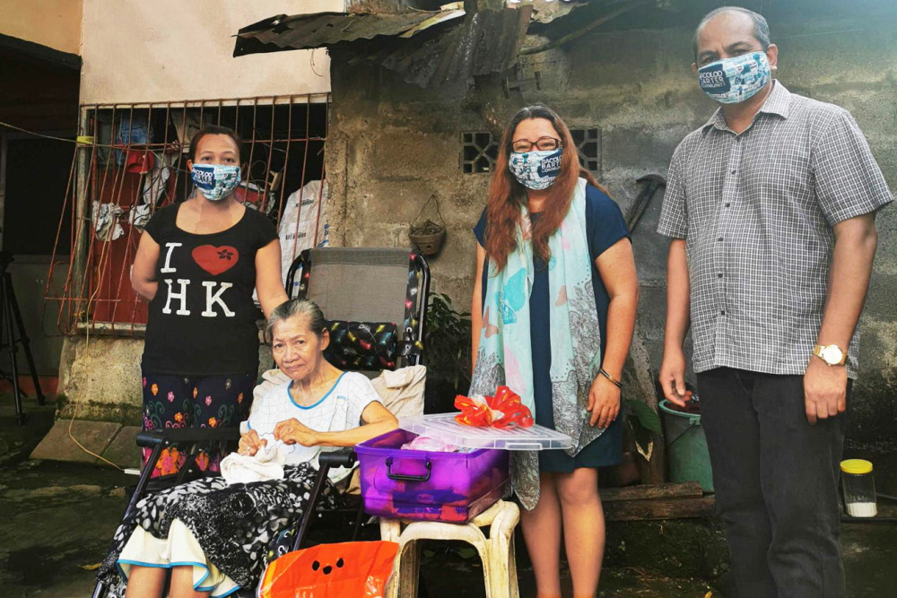 Jocelle Batapa Sigue (thứ hai từ phải sang) cùng chồng Arnel (bìa phải) giúp Sheila Rapada (trái) đổi bưởi lấy thức ăn và thuốc cho bà Nenita (ngồi xe lăn) thông qua Cộng đồng đổi hàng Bacolod - Ảnh: AFP