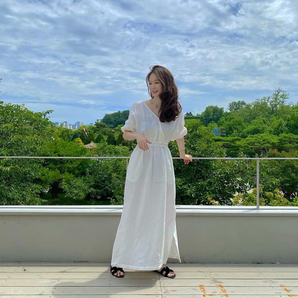 Kang Min-kyung ngây thơ và ngọt ngào khi diện lên mình chiếc váy lanh dài. Đường xẻ ngực sâu và chích eo giúp thiết kế mang đến cảm giác nữ tính. Đừng quên phối thêm một số phụ kiện như vòng tay, nhẫn...
