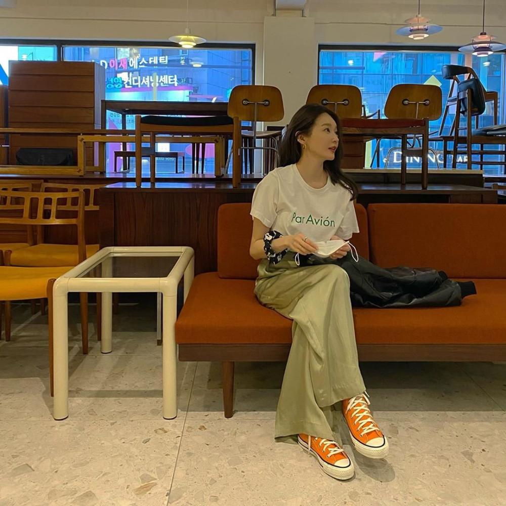 Ngoài quần jean, áo thun trắng còn phù hợp với nhiều loại quần khác nhau. Giống như Kang Min-kyung, cô không ngần ngại kết hợp với quần ống rộng màu xanh lá cây, được xem là một trong những item khó tạo kiểu. Phái đẹp nên tinh tế chọn phông chữ in trên áo trùng hợp màu của quần tạo nên hiểu quả tối ưu. Tưởng không ăn nhập với nhau nhưng đôi giày Converse màu cam được nữ ca sĩ phồi cùng, ngược lại còn mang đến vẻ ngoài sanh điệu và cực kỳ thu hút.