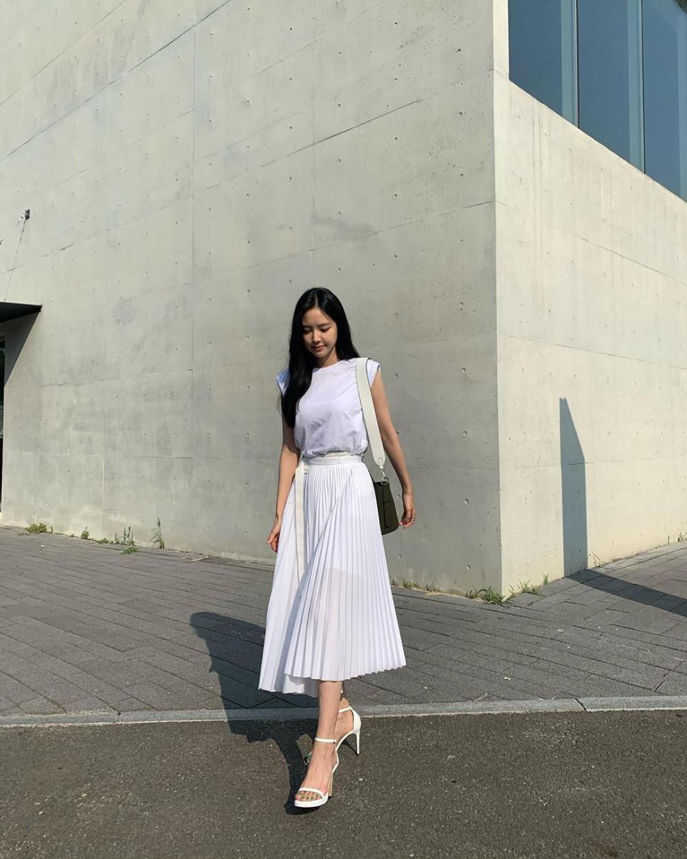 Son Na-eun xinh đẹp khi diện nguyên set đồ màu trắng. Cô chọn áo phông cộc tay với phần đường viền tinh tế kết hợp cùng chân váy xếp ly nữ tính. Nữ ca sĩ không quên sử dụng giày cao gót giúp vóc dáng thanh thoát hơn.
