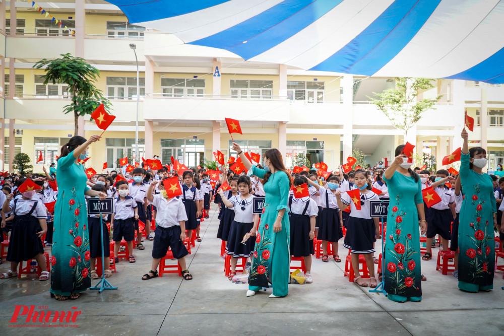 Các em vẫy cờ chào mừng đại biểu vè thăm trường