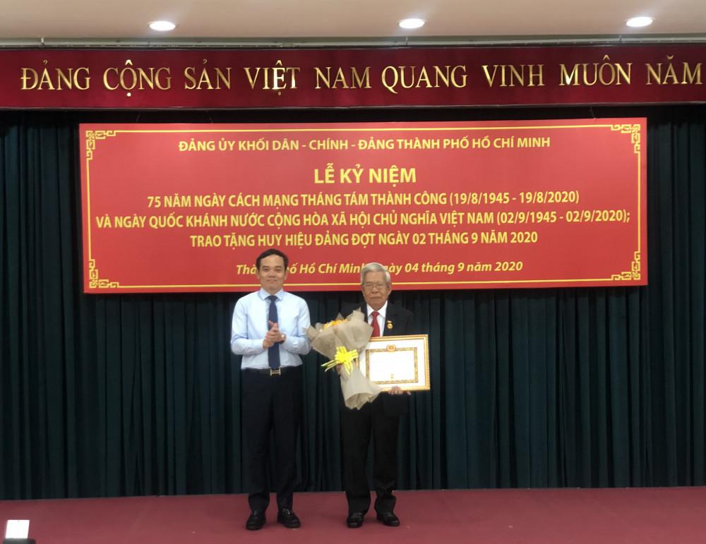 Ông Trần Lưu Quang - Phó Bí thư thường trực Thành ủy TPHCM - trao Huy hiệu 60 năm tuổi Đảng cho ông Lê Tâm Dũng (Đảng bộ cơ quan Văn phòng Thành ủy). Ảnh: Quốc Ngọc