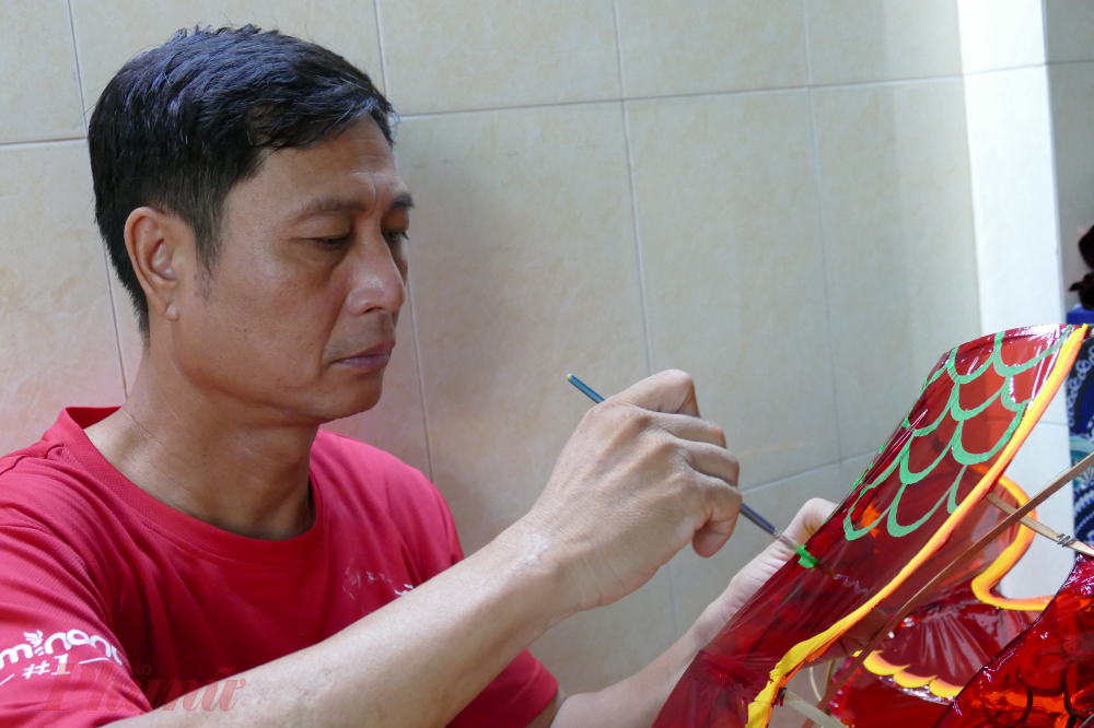 Anh Nguyễn Thành chăm chú bên từng công đoạn để hoàn thiện chiếc lồng đèn. Theo anh Thành, người làm lồng đèn phải nắm rõ các công đoạn như: làm khung, vẽ hình, trang trí…