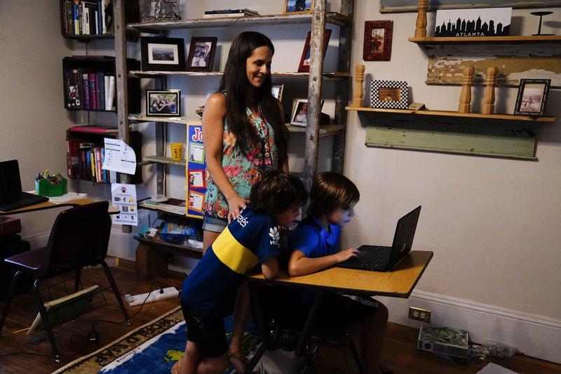 Anna Hamilton, 43 tuổi, đang hướng dẫn hai con Henry (6 tuổi) và Adrian (7 tuổi) học từ xa ở nhà. Không có ai ở nhà với con, cô đã phải nghỉ việc tại một công ty đầu tư nhỏ nơi cô đã làm việc 12 năm ở Decatur, Georgia - Ảnh: AP