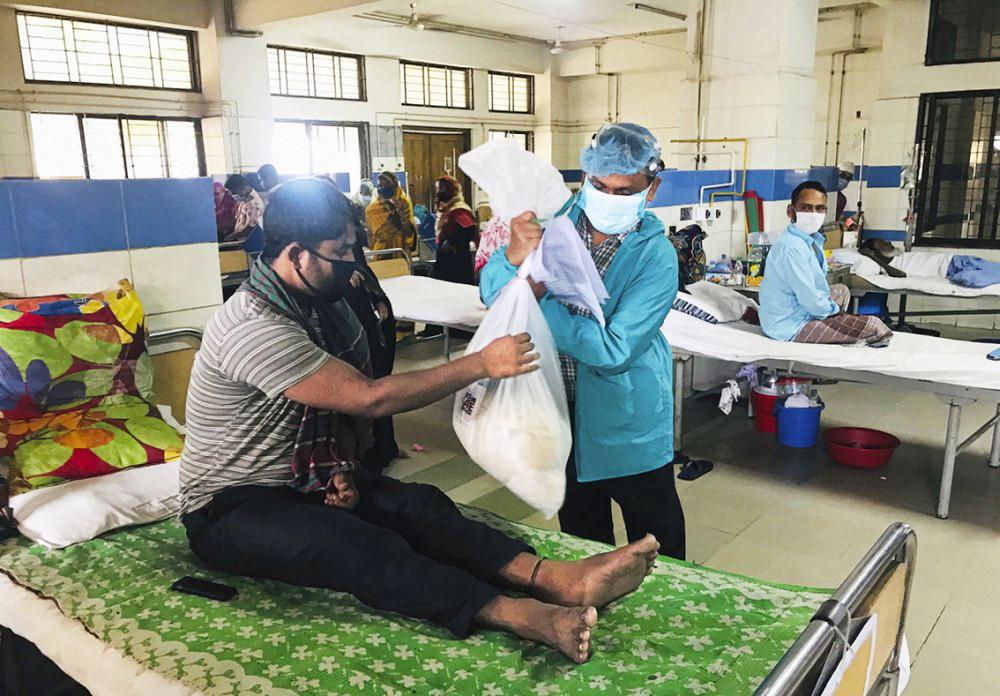 Một tình nguyện viên của Mission Save Bangladesh phân phát thực phẩm cho bệnh nhân nghèo tại một bệnh viện ung thư ở Dhaka, Bangladesh