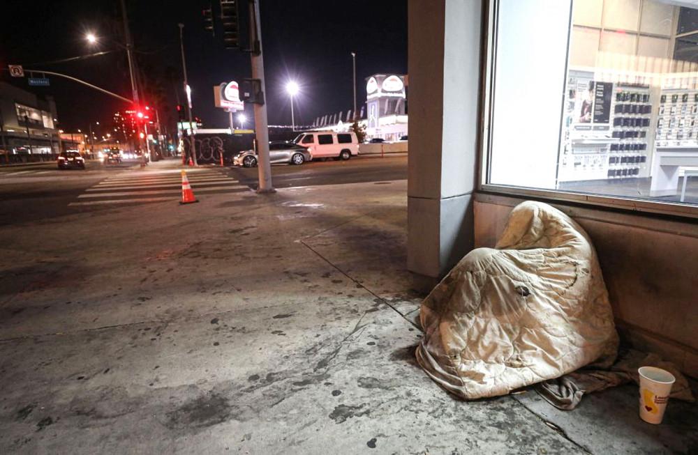 Một người vô gia cư co mình dưới tấm chăn bên lề đại lộ Sunset ở TP.Los Angeles Ảnh: Getty Images