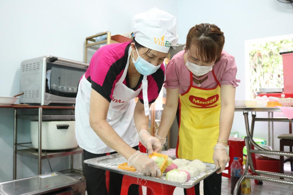 Cán bộ, hội viên phụ nữ phường Trường Thọ chia thành nhiều nhóm, chỗ lo nhồi bột, làm nhân, chỗ đưa bánh vào khuôn, nướng bánh.