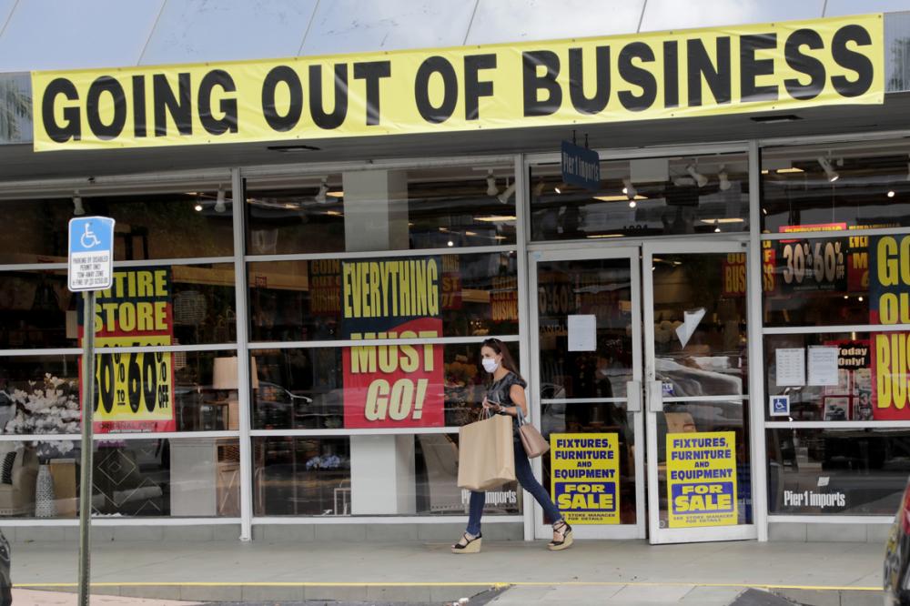 Một khách hàng rời khỏi cửa hàng bán lẻ sắp ngừng kinh doanh vì đại dịch COVID-19 - Ảnh: AP