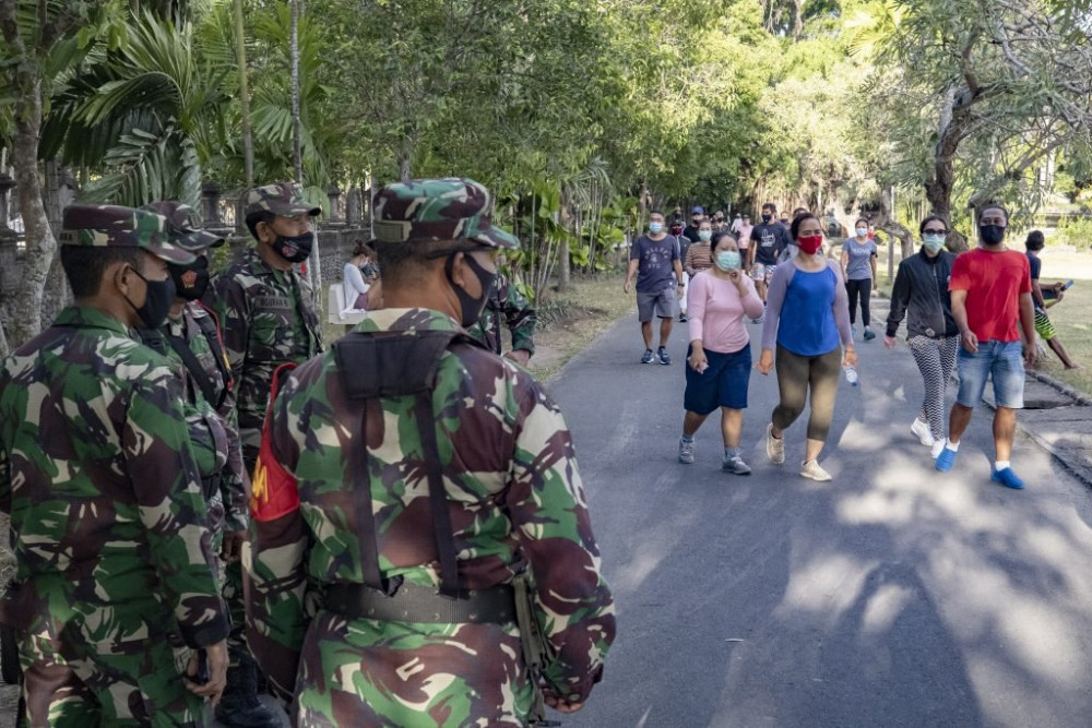Cảnh sát Bali kiểm tra việc thực hiện chính sách đeo khẩu trang và phòng dịch của du khách tại hòn đảo nổi tiếng của Indonesia.