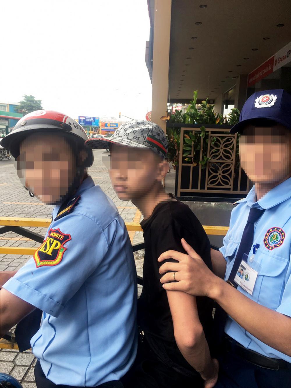 Thiếu niên (ngồi giữa) bị bảo vệ bắt giữ khi đang quay lén phụ nữ trong nhà vệ sinh của một trung tâm thương mại ở Q.Gò Vấp, TP.HCM