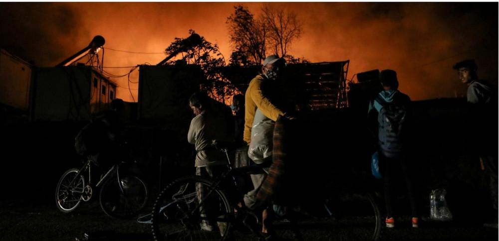 Những người tị nạn và di cư mang theo đồ đạc của họ khi họ chạy trốn khỏi ngọn lửa đang bùng cháy tại trại Moria trên đảo Lesbos