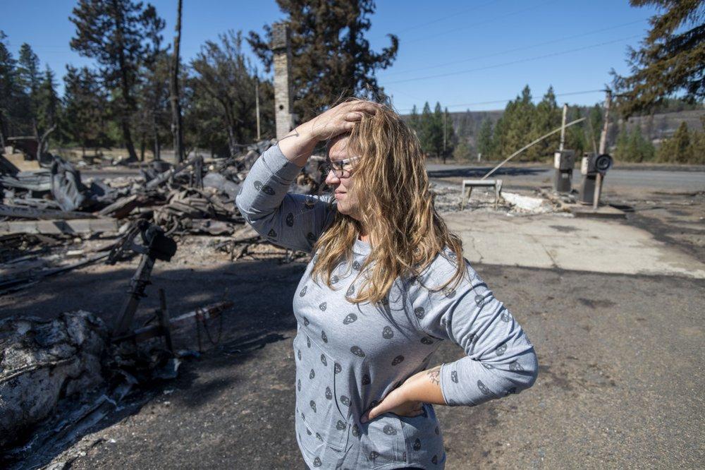 Hollie Jordan đứng nhìn trạm dịch vụ nông nghiệp của cha cô ở Malden (Washington) bị trận cháy rừng hôm 8/9 thiêu hủy - Ảnh: AP
