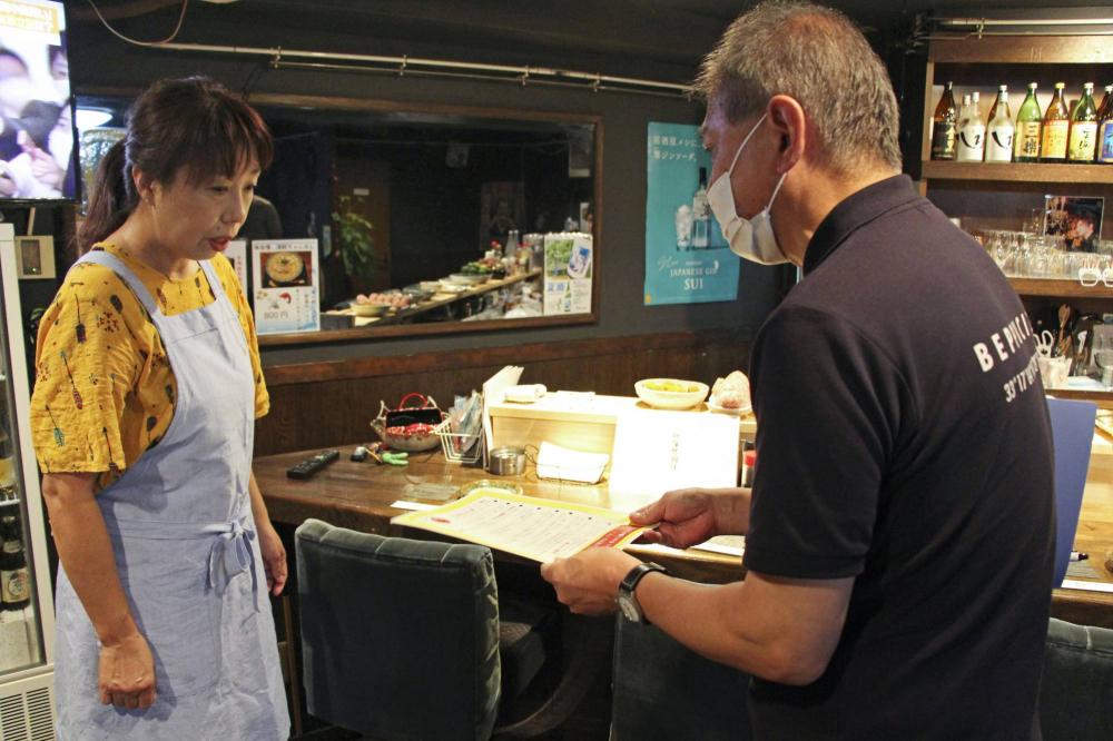 Một quan chức thành phố Beppu phát thông báo nhắc nhở doanh nghiệp không phân biệt đối xử với cư dân nước ngoài trong bối cảnh đại dịch COVID-19 - Ảnh: KYODO